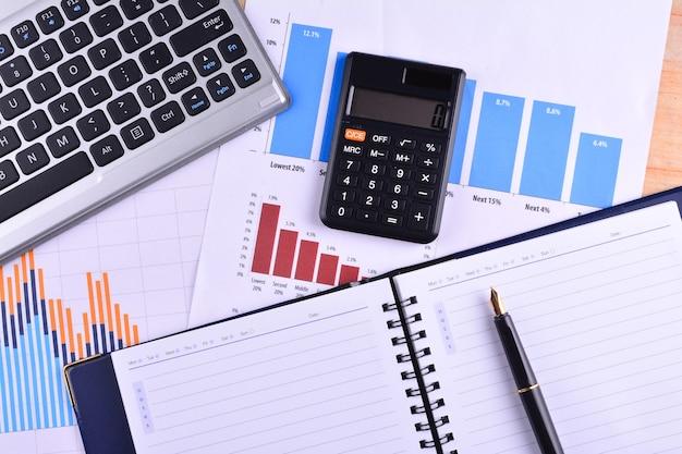 Blanco notitieboekje met rekenmachine, toetsenbord en vulpen op grafieken, grafieken en zakelijke tafel. de werkplek van zakenmensen