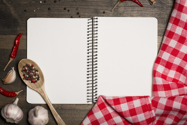 Blanco notitieboekje op de keukentafel met chili paprika's en kruiden