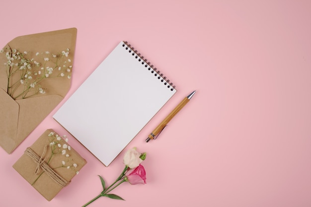 Blanco pagina met envelop en huidige doos op roze tafel