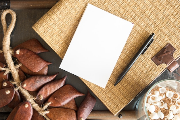Blanco papier en pen met vintage mandenmakerswerk en droge pod achtergrond