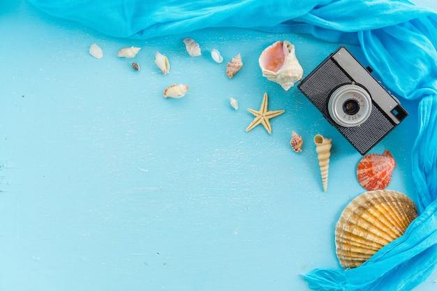 Blanco papier fotolijst met zeesterren, schelpen en items op houten tafel.