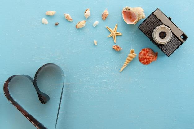Blanco papier fotolijsten met zeesterren, schelpen en items op houten tafel.