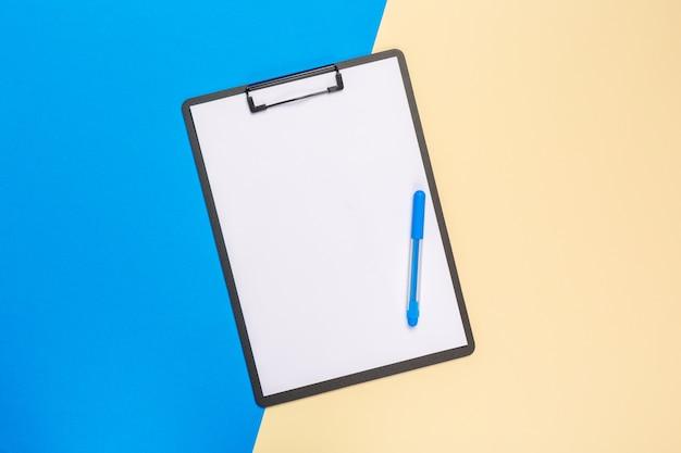 Blanco papier kladblok op heldere tweekleurige achtergrond voor uw ontwerp, bovenaanzicht