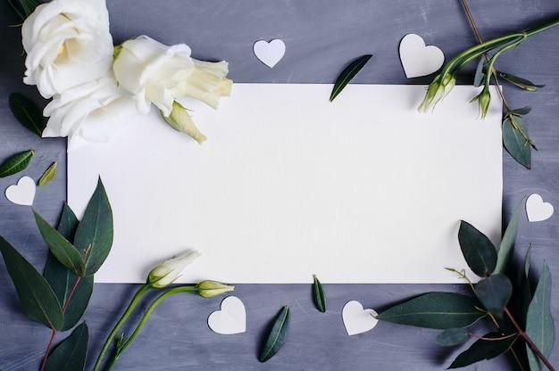 Blanco papier kopie ruimte. kader met bloemen. zijden lint. grijze achtergrond. eenvoudig boeket. wenskaart.