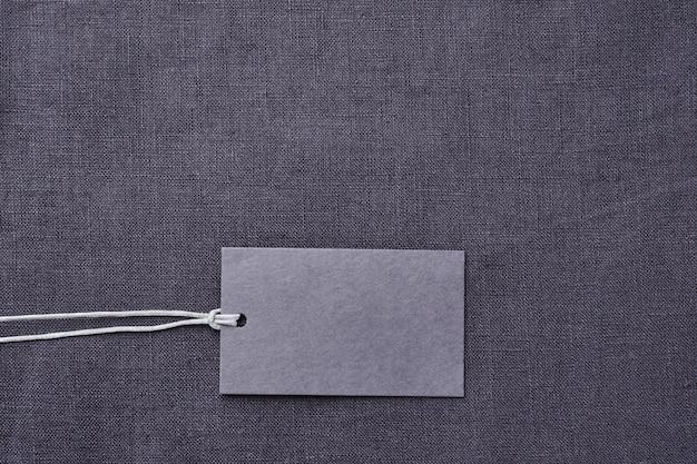 Blanco papier label op grijze linnen kleding