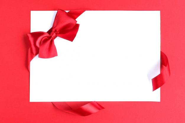 Blanco papier leeg met rode satijnen strik op witte tafel.