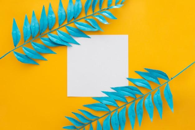 Blanco papier met blauwe bladeren op gele achtergrond