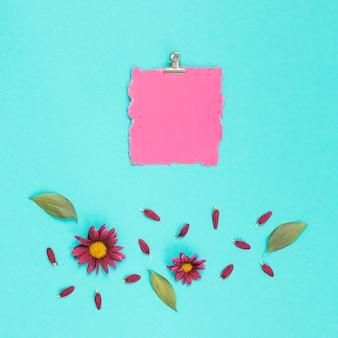 Blanco papier met bloemen op blauwe tafel