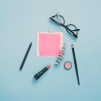 Blanco papier met een bril en lippenstift op tafel