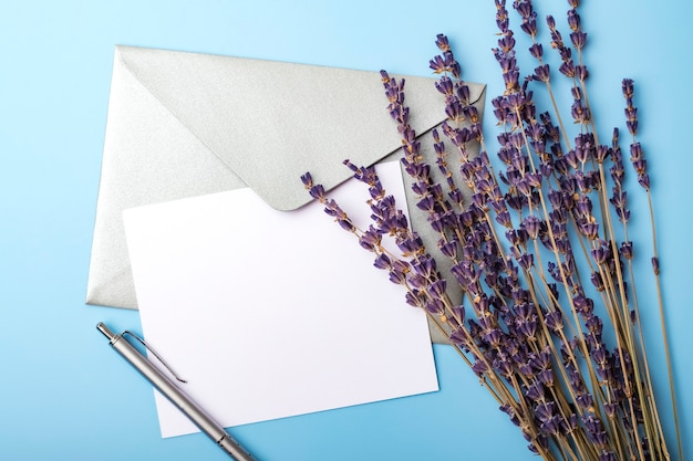 Blanco papier met envelop en lavendelbloemen op een blauwe achtergrond. eenvoudige trouwkaart. uitzicht van boven