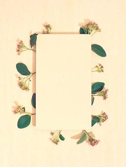 Blanco papier met frame van bloemen. plat leggen, ruimte kopiëren, bovenaanzicht.