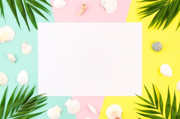 Blanco papier met palmbladeren en schelpen