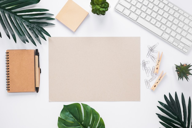 Blanco papier omgeven met kantoorbenodigdheden op witte werkruimte