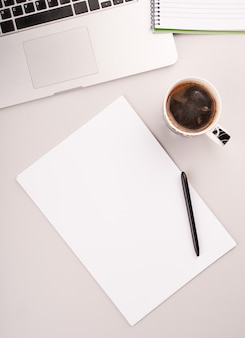 Blanco papier op het bureau met computer en koffie