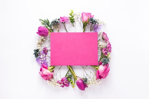 Blanco papier op verschillende bloemen op tafel