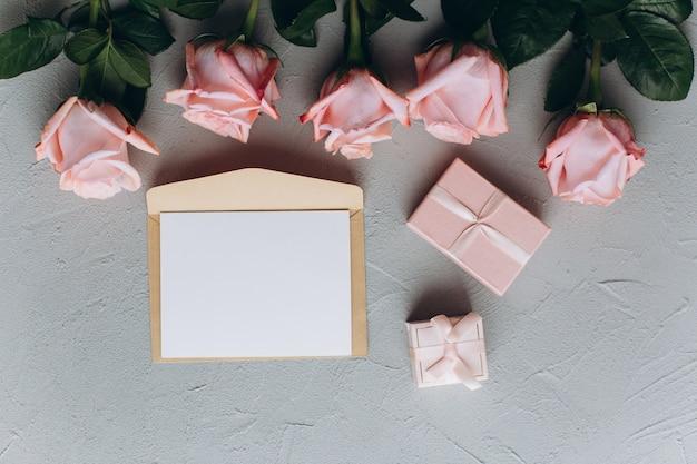 Blanco papier opmerking met envelop, geschenken en roze roos