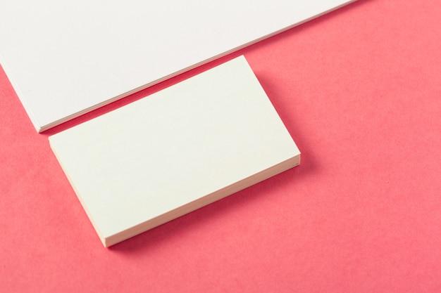Blanco papier stukken op een gekleurde roze achtergrond