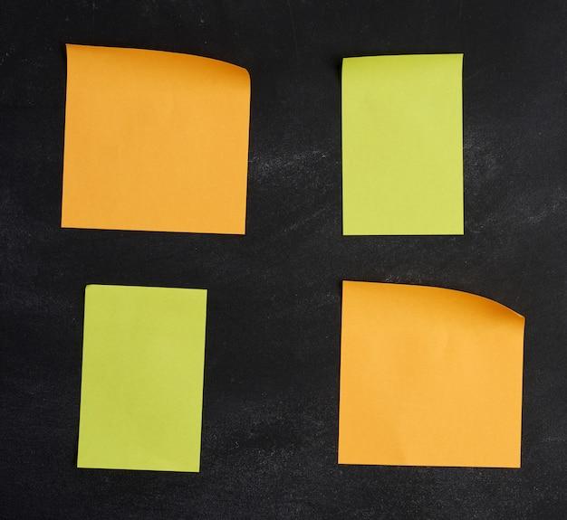 Blanco papier veelkleurige vierkante stickers zijn geplakt op een zwart krijtbord