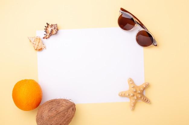 Blanco papier, zonnebril, exotisch fruit, schelpen en zeester op gele achtergrond. concept van zomervakantie