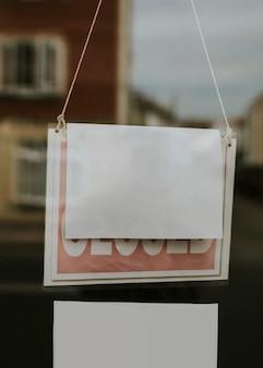 Blanco papieren bord hangend aan een gesloten etalage