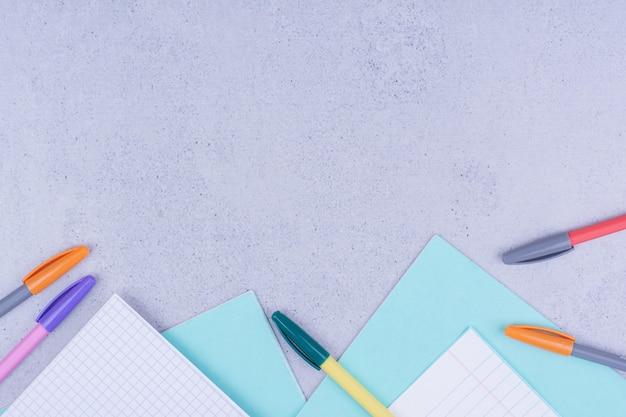 Blanco papieren en kleurrijke potloden op grijze ondergrond