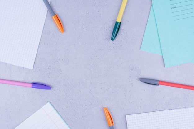 Blanco papieren en pennen geïsoleerd op grijs.
