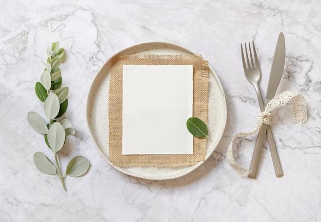 Blanco papieren kaart leggen op plundering op witte plaat met vork en mes op marmeren tafel met eucalyptus takken en vintage linten, bovenaanzicht. mockup voor huwelijksuitnodiging