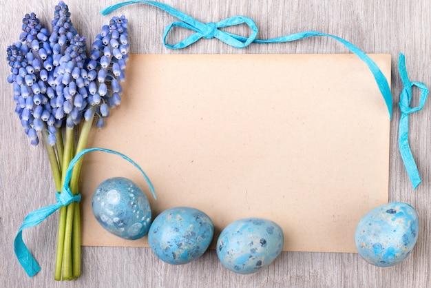Blanco papieren kaart omlijst door blauwe linten, paaseieren en druivenhyacint bloemen, tekstruimte