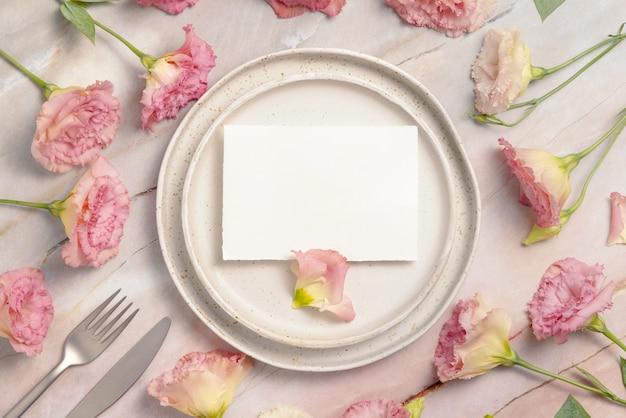Blanco papieren kaart op beige plaat op marmeren tafel met roze bloemen eromheen, bovenaanzicht. mockup voor huwelijksuitnodiging
