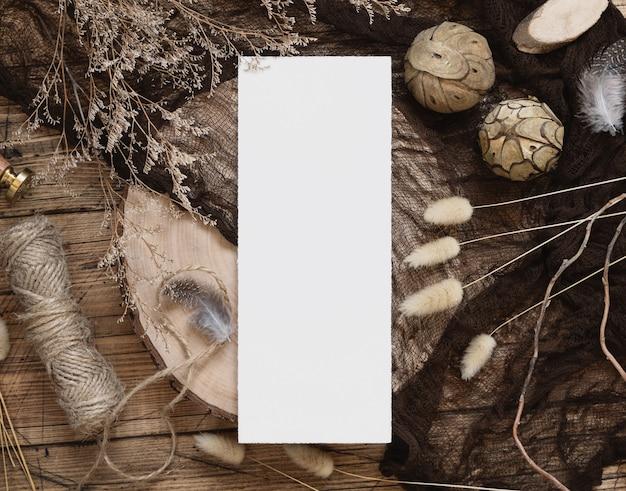 Blanco papieren kaart op een houten tafel met gedroogde planten rond, bovenaanzicht. boho-modelscène met menukaartsjabloon