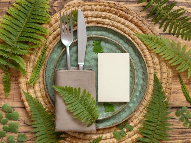 Blanco papieren kaart op tafel instelling versierd met varenbladeren op houten tafelblad weergave. tropische mock-upscène met plat gelegde plaatskaart