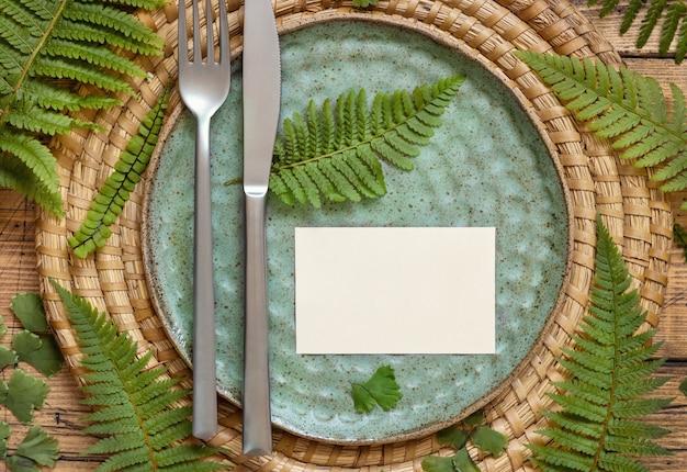 Blanco papieren kaart op tafel instelling versierd met varenbladeren op houten tafelblad weergave. tropische mock-upscène met plat gelegde plaatskaart Premium Foto