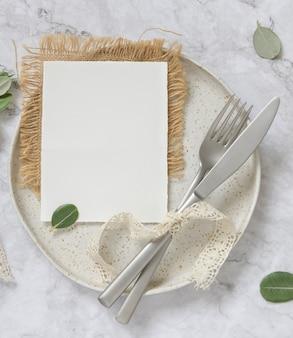Blanco papieren kaart opleggen van witte plaat met vork en mes op marmeren tafel met eucalyptus takken en vintage linten rond, bovenaanzicht. kaartmodel