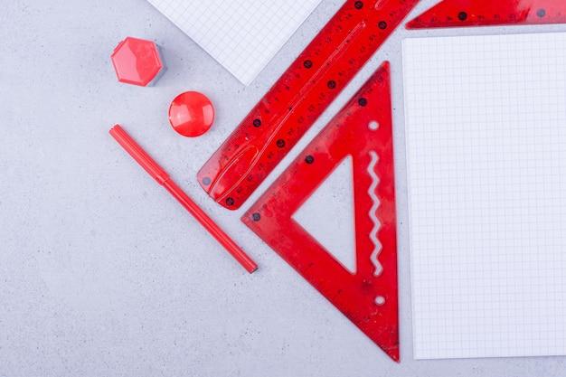 Blanco papieren met rode pinnen en linialen