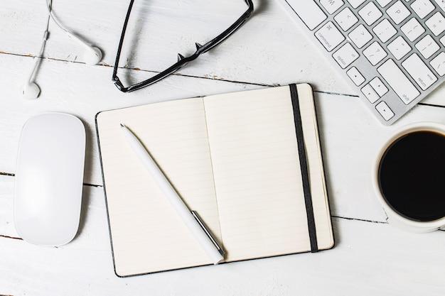 Blanco papierwerk sjabloon voor ontwerpers. responsieve design mockup op vintage houten achtergrond. papier, briefhoofd, koffiekopje, smartphone, potlood en koptelefoon op houten tafelachtergrond. bovenaanzicht.
