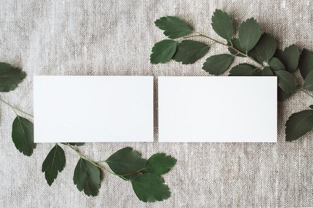 Blanco persoonlijke kaartpapiermodellen met natuurlijk zonlicht en botanische schaduwen op grijs linnen