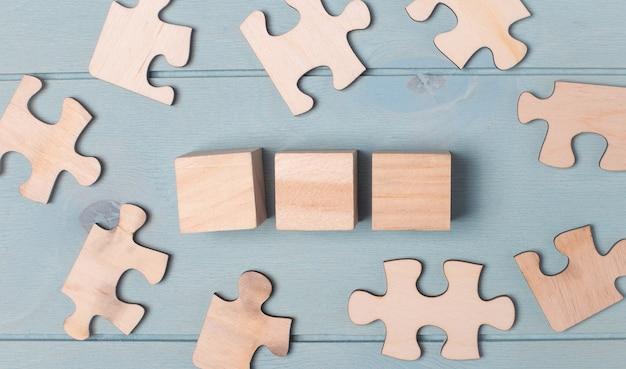 Blanco puzzels en houten blokjes liggen op een lichtblauw oppervlak