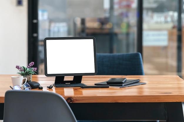 Blanco schermtablet met standaardhouder en gadget op houten tafel in co-werkruimte