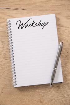 Blanco spiraalvormig notitieboekje met een workshop-kop en lege regels op een houten tafel en een metalen zilveren pen erop.