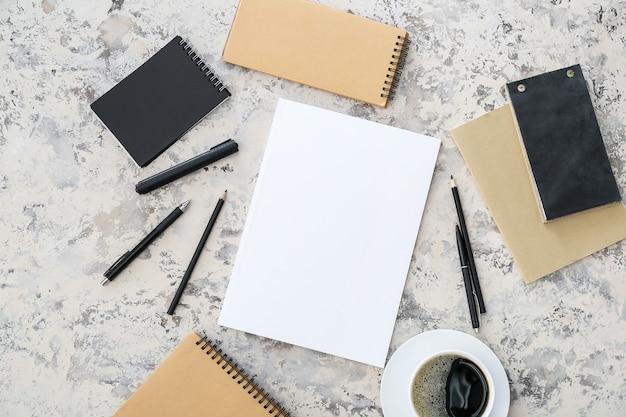 Blanco tijdschrift, kopje koffie en notitieboekjes