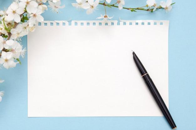 Blanco vel kladblok met kopie ruimte. vlakbij een inktpen, bindmiddelen, een tak bloemen op een blauwe achtergrond. lente concept voor uw teksten.