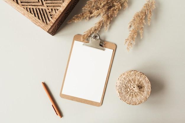Blanco vel klembord met lege kopie ruimte, pen, rotankist op neutraal