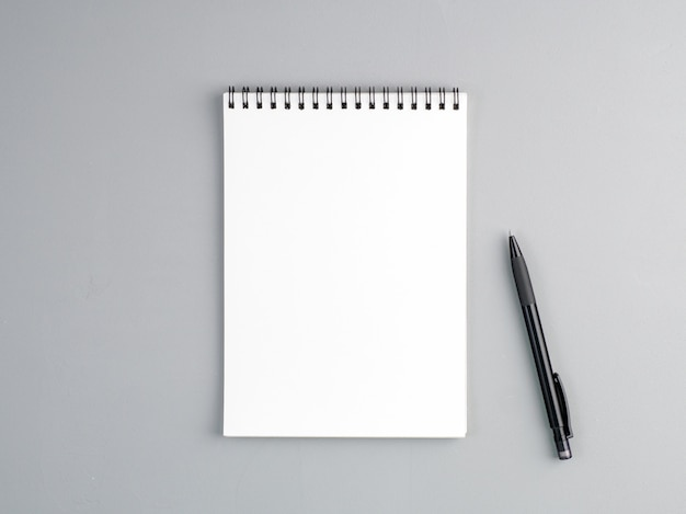 Blanco vel notebook een spiraal en pen op een neutrale grijze gestructureerde achtergrond