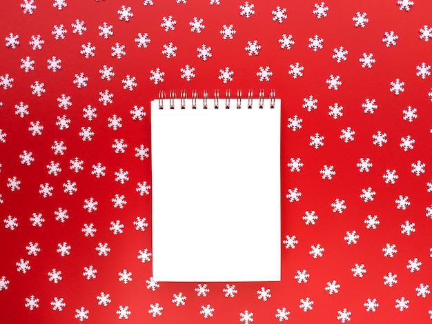Blanco vel notebook met verspreide witte sneeuwvlokken op rode achtergrond. educatief concept. eenvoudig plat leggen met kopie ruimte.