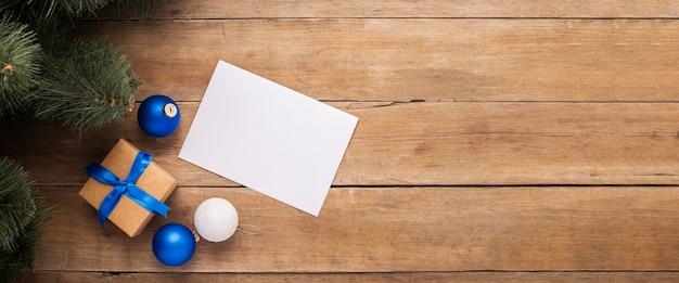 Blanco vel papier en een cadeau onder de kerstboom op een houten ondergrond. bovenaanzicht, plat gelegd. banier.