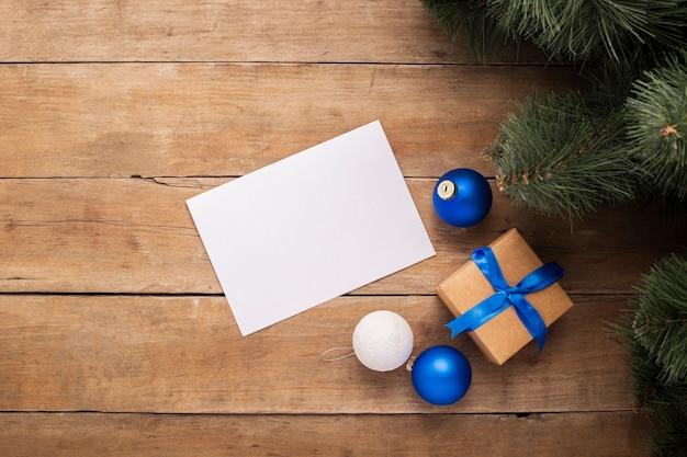 Blanco vel papier en een cadeau onder de kerstboom op een houten ondergrond. bovenaanzicht, plat gelegd.