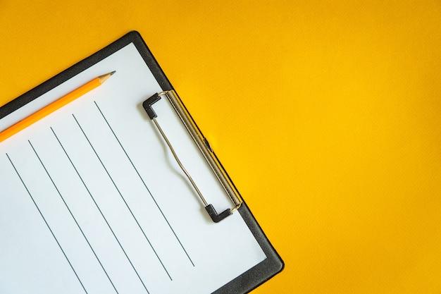 Blanco vel papier en een potlood op geel bureau