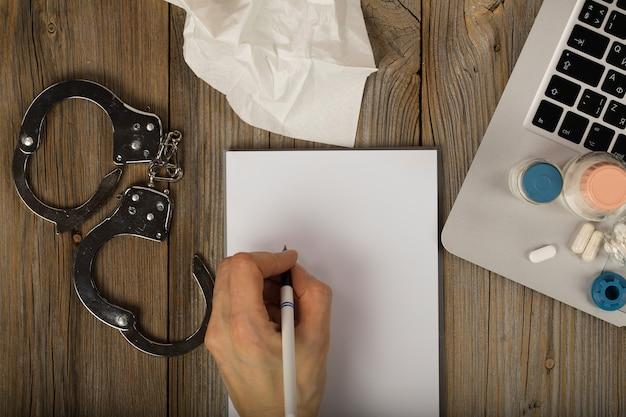 Blanco vel papier en menselijke hand. farmaceutische producten en handboeien op een houten oppervlak. detailopname