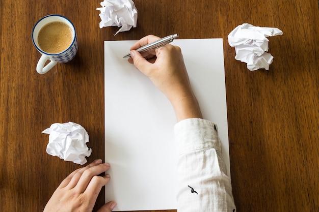Blanco vel papier en pen op heldere houten bureau met handen van een persoon