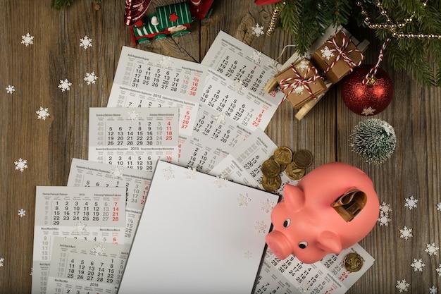 Blanco vel papier en roze spaarvarken op een nieuwjaarsachtergrond bovenaanzicht
